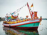 """23 JUNE 2015 - MAHACHAI, SAMUT SAKHON, THAILAND: The fishing boat carrying the City Pillar Shrine up the Tha Chin (Chin River) in Mahachai. The Chaopho Lak Mueang Procession (City Pillar Shrine Procession) is a religious festival that takes place in June in front of city hall in Mahachai. The """"Chaopho Lak Mueang"""" is  placed on a fishing boat and taken across the Tha Chin River from Talat Maha Chai to Tha Chalom in the area of Wat Suwannaram and then paraded through the community before returning to the temple in Mahachai.   PHOTO BY JACK KURTZ"""
