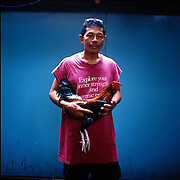 THE PHILIPPINES (Manila). 2009. David Afable, 30, with his game cock before the cockfighting at the La Loma Cockpit,  Manila. Photo Tim Clayton <br /> <br /> Cockfighting, or Sabong as it is know in the Philippines is big business, a multi billion dollar industry, overshadowing Basketball as the number one sport in the country. It is estimated over 5 million Roosters will fight in the smalltime pits and full-blown arenas in a calendar year. TV stations are devoted to the sport where fights can be seen every night of the week while The Philippine economy benefits by more than $1 billion a year from breeding farms employment, selling feed and drugs and of course betting on the fights...As one of the worlds oldest spectator sports dating back 6000 years in Persia (now Iran) and first mentioned in fourth century Greek Texts. It is still practiced in many countries today, particularly in south and Central America and parts of Asia. Cockfighting is now illegal in the USA after Louisiana becoming the final state to outlaw cockfighting in August this year. This has led to an influx of American breeders into the Philippines with these breeders supplying most of the best fighting cocks, with prices for quality blood lines selling from PHP 8000 pesos (US $160) to as high as PHP 120,000 Pesos (US $2400)..