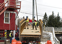 Crew workers secure the metal footbridge to be hoisted in place at Perley Canal and Jewett Brook behind the Laconia Spa on Church Street Thursday morning.  (Karen Bobotas/for the Laconia Daily Sun)