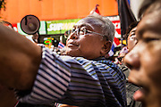 """20 DECEMBER 2013 - BANGKOK, THAILAND: SUTHEP THAUGSUBAN, leader of the anti-government protests, works the crowd during a march on Silom Road in Bangkok. Thousands of anti-government protestors, supporters of the so called Peoples Democratic Reform Committee (PRDC), jammed the Silom area, the """"Wall Street"""" of Bangkok, Friday as a part of the ongoing protests against the caretaker government of Yingluck Shinawatra. Yingluck dissolved the Thai Parliament earlier this month and called for national elections on Feb. 2, 2014. The protestors want the elections postponed and the caretaker government to step down. The Thai election commission ruled Friday that the election would go on dispite the protests.          PHOTO BY JACK KURTZ"""