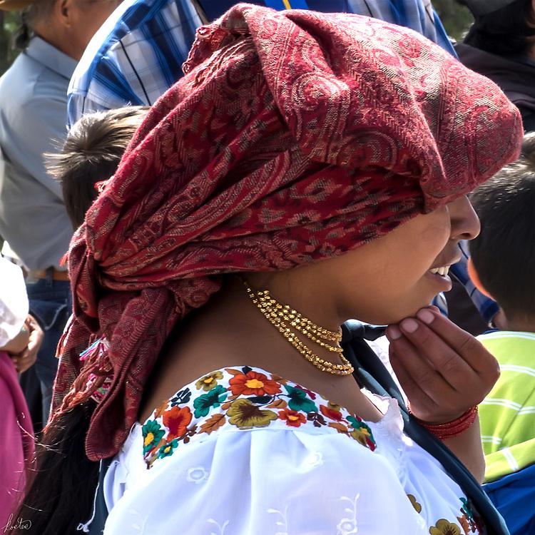 A Kichwa Woman in a red headress at a Kapak Raymi Celebration