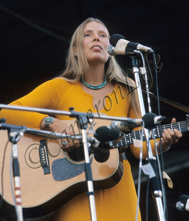 """Joni Mitchell .- .Born as Roberta Joan Anderson in 1943, Joni Mitchell was instrumental in penning such great songs as """"Both Sides Now"""" (later made famous by Judy Collins) and her own hit """"Big Yellow Taxi"""". The Isle of Wight festival wasn't her greatest moment however, as her stage appearance was initially repeatedly interrupted by protesters, finally reduced her to tears."""