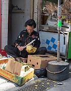 Woman cleaning fruit in Kat Hing Street, Tai O Fisging Village, Lantau Island, Hong Kong, China.