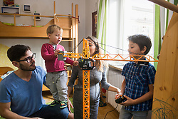 Two brothers and parents are playing with a toy crane, Munich, Germany