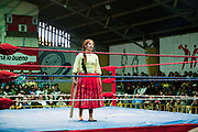 Alicia Flores female wrestler chasing male opponent with a wooden plank, in ring with crowd in background. Lucha Libre wrestling origniated in Mexico, but is popular in other latin Amercian countries, including in La Paz / El Alto, Bolivia. Male and female fighters participate in the theatrical staged fights to an adoring crowd of locals and foreigners alike.