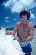 researcher Charles Pike implants ultrasonic transmitter into lemon shark, Negaprion brevirostris, for tracking, during University of Miami shark research at Bimini Biological Field Station, aka SharkLab, Bimini, Bahamas ( Western Atlantic Ocean )