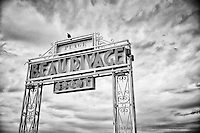 Black and white view of the Plage Beau Rivage Sport Hotel and Restaurant sign found along the Promenade des Anglais, Nice, France.