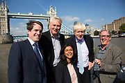 London, UK. Monday 8th September 2014. London Mayor Boris Johnson with Derek Ray-Hill (Business development Director of London First), Robert Gordon Clark (Chair of the Thames Festival Trust), Munira Mirza (Deputy Mayor for Education and Culture), and Adrian Evans (Director of Totally Thames), holding a bottle of water drawn from the source of the Thames with Tower Bridge as the backdrop. The bottle has been carried in Olympic torch fashion by hundreds of people conveying the bottle from the source to the mouth of the Thames. A highlight of Totally Thames, the new month-long promotion of river and riverside events delivered by Thames Festival Trust.