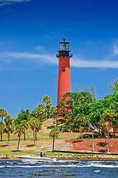 Jupiter Inlet Lighthouse, restored 1860 historic lightouse, and sport fishing boat in Loxahatchee River, Florida, Atlantic Ocean