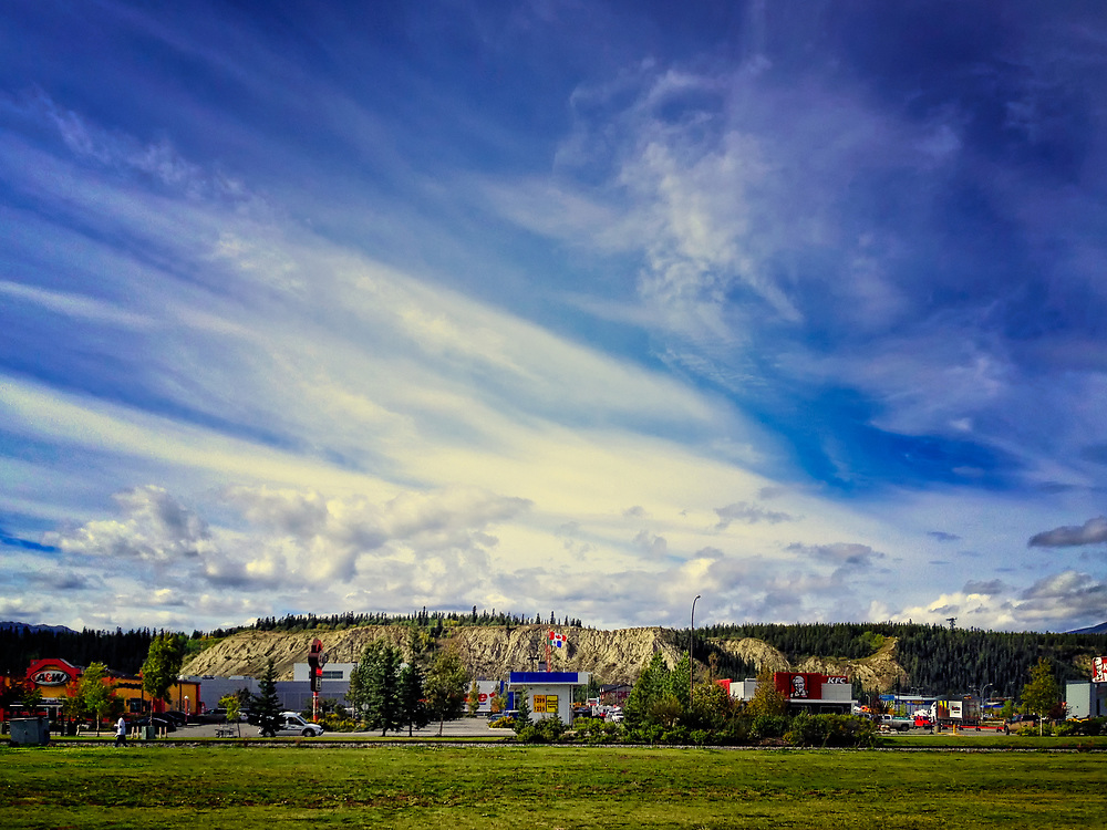 The outskirts of Whitehorse as seen from the edge of the Yukon River  / Waterfront Walkway looking North. Note the proliferation of American restaurant chains (A&W, KFC) with the Canadian flag proudly at full mast mid-bottom of frame.