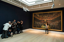 © Licensed to London News Pictures. 27/09/2019. London, UK. A Sotheby's staff views a painting titled Devolved Parliament, 2009, by artist Banksy. The painting depicts MP's in the houses of Parliament with an estimate of £1.5-2 million. The work is part of the Sotheby's contemporary art auction. Photo credit: Ray Tang/LNP