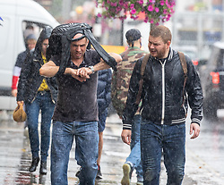 © Licensed to London News Pictures. 19/08/2020. London, UK. Shoppers get caught in heavy rain and gusty winds on the Kings Road in Kensington in South West London today as storm Ellen hits the UK. Weather forecasters have predicted torrential rain and high winds before a warmer front develops this week with sunnier weather and highs of 24c. Photo credit: Alex Lentati/LNP