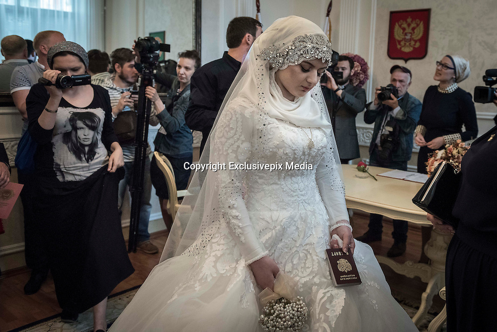 Tears on her wedding day: Heartbreaking pictures capture moment forlorn teenage bride was forced to marry a polygamous Chechen police chief after 'he threatened her with kidnap'<br /> <br /> Her resplendent white dress says it's her wedding day, but the sadness etched on her face does not.<br /> For this teenage bride has been forced to marry an ally of Chechen warlord Ramzan Kadyrov after apparently being threatened with kidnap if she did not comply.<br /> Kheda Goilabiyeva, 17,looked despondent and at one point wept during the ceremony in the Chechen capital Grozny as the fearsome Kadyrov watched on from the crowd.<br /> She was asked three times whether she wanted to marry 47-year-old police chief Nazhud Guchigov– who already has another wife–before finally and reluctantly responding yes.<br /> <br /> <br /> The marriage has provoked outrage in Russia, fuelled by Moscow's child rights commissioner, Pavel Astakhov, who defended the wedding by saying that Caucasian women 'are all shrivelled with wrinkles by the age of 27'.He later apologised for his comments.<br /> In response to the remarks, young women online have started posting selfies on Instagram with the hashtag #WrinkledWoman in which they scrunch up their faces to simulate the appearance of wrinkles. Many of the posts include sarcastic greetings to Astakhov.<br /> <br /> <br /> The woman behind the campaign appears to be Bella Rapoport, a prominent Russian feminist writer, according to Instagram's time stamps.<br /> The second contributor appears to be Tonia Samsonova, a popular journalist at Echo of Moscow with a large online social media following.<br /> Within 12 hours, the hashtag has attracted more than 120 contributions.<br /> <br /> Kadyrov, who has ruled Chechnya with an iron fist since being installed by Russian President Vladimir Putin in 2007, was said to have given his personal blessing for the marriage in apparent violation ofRussian laws against polygamy.<br /> The procession then carried on 