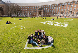 © Licensed to London News Pictures;11/04/2021; Bristol, UK. People wave and give the thumbs up sign as they enjoy the spring weather and sunshine sitting inside socially distanced heart shapes on College Green and other open spaces in the city which have been painted with Love Bristol stencils during the Covid-19 coronavirus pandemic in England as lockdown restrictions are due to be eased further on Monday 12 April. This is the #LoveBristol campaign to welcome visitors back to the city safely and support local businesses as they reopen from Monday. Photo credit: Simon Chapman/LNP.