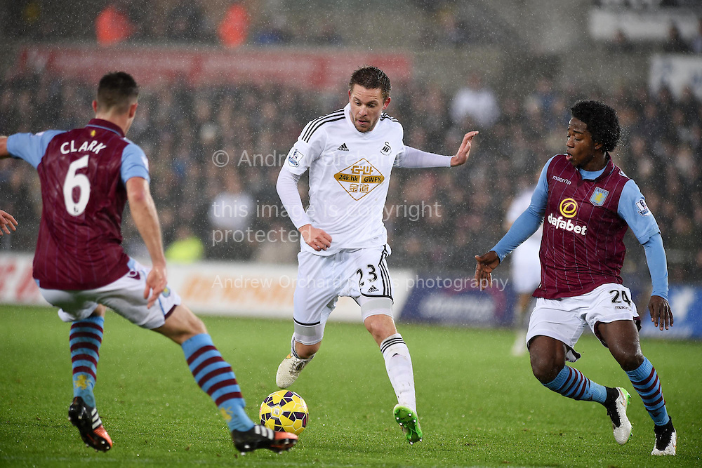 Gylfi Sigurdsson of Swansea city © looks to go past Aston Villa's Cieran Clark (6) and Carlos Sanchez (24). Barclays Premier league match, Swansea city v Aston Villa at the Liberty stadium in Swansea, South Wales on Boxing Day, Friday 26th December 2014<br /> pic by Andrew Orchard, Andrew Orchard sports photography.