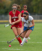 Laconia's Lauren McDonald and Gilford's Brianna Salinitro charge the ball during NHIAA Division III field hockey on Wednesday.  (Karen Bobotas/for the Laconia Daily Sun)