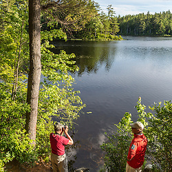 A woman photographs Page Pond in Meredith, New Hampshire.