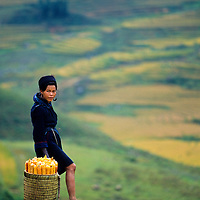 Black Hmong girl takes a break from carrying corn through the mountains of Sapa, Vietnam