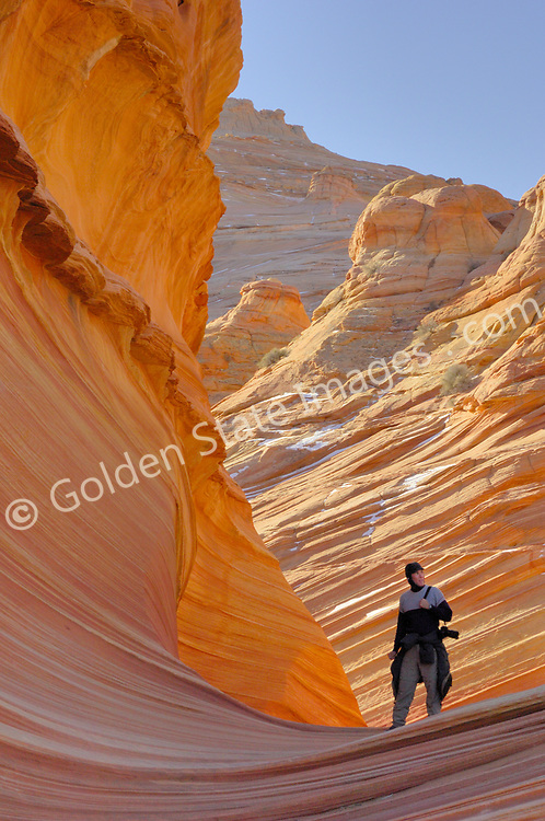 """A hiker standing at the entrance to The Wave, Paria Canyon - Vermillion Cliffs Wilderness area, Southern Utah.<br /> <br /> Coyote Buttes North located in the Paria Canyon - Vermilion Cliffs Wilderness. This area features one of the most well-known geologic sandstone formations in the world, called """"The Wave"""".<br /> <br /> The Wave is a spectacular area of sandstone formations twisted into the shapes of breaking waves pillars cones and mushrooms.<br /> <br /> An ancient sea laid down layers of sediment deposits which hardened to form the multicolored sandstone rock. Over eons the actions of water the cycles of baking heat and subfreezing temperatures and wind have formed its complex undulating shapes.<br /> <br /> The deep reds of the rock and their shapes appear to change with the seasons and time of day."""