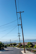 Tall telephone poles carrying PG&E power lines lean slightly over a neighborhood street in the El Cerrito Hills with view of downtown San Francisco between them.