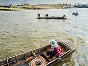 14 OCTOBER 2015 - BANGKOK, THAILAND:   Salvage divers work the Chao Phraya River in Bangkok. Divers work in two man teams on small boats in the Chao Phraya River. One person stays in the boat while the diver scours the river bottom for anything that can be salvaged and resold. The divers usually work close to shore because the center of the river is a busy commercial waterway with passenger boats and commercial freight barges passing up and down the river all day long. The Chao Phraya is a dangerous river to dive in. It's deep, has large tidal fluctuations, is fast flowing and badly polluted. The divers make money only when they sell something.      PHOTO BY JACK KURTZ