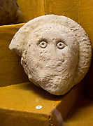 Human face carved onto an ammonite, using the natural form of the fossil. Found in Great Bedwyn. With permission of Wiltshire Museum, Devizes, England, UK