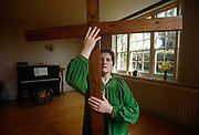 In front of an upright piano and spring daffodils on a window ledge, we see a lady member of the evangelical Sacred Dance Ministry (Group) wearing a green velvet tunic while holding a wooden cross, standing in an otherwise empty room belonging to this Christian group in Milbourne St Andrew, Dorset, England. As part of the International Christian Dance Fellowship whose performers include performers, choreographers and teachers of all styles of dance technique, as well as those who dance in worship, intercession, healing, evangelism and prophetic interpretation and this lady has recreated a moment in one of their performances.