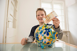 Smiling boy with piggy bank and 50 Euro note