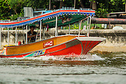 "17 NOVEMBER 2012 - BANGKOK, THAILAND:  A river taxi on the Chao Phraya River in Bangkok. Bangkok used to be known as the ""Venice of the East"" because of the number of waterways the criss crossed the city. Now most of the waterways have been filled in but boats and ships still play an important role in daily life in Bangkok. Thousands of people commute to work daily on the Chao Phraya Express Boats and fast boats that ply Khlong Saen Saeb or use boats to get around on the canals on the Thonburi side of the river. Boats are used to haul commodities through the city to deep water ports for export.    PHOTO BY JACK KURTZ"