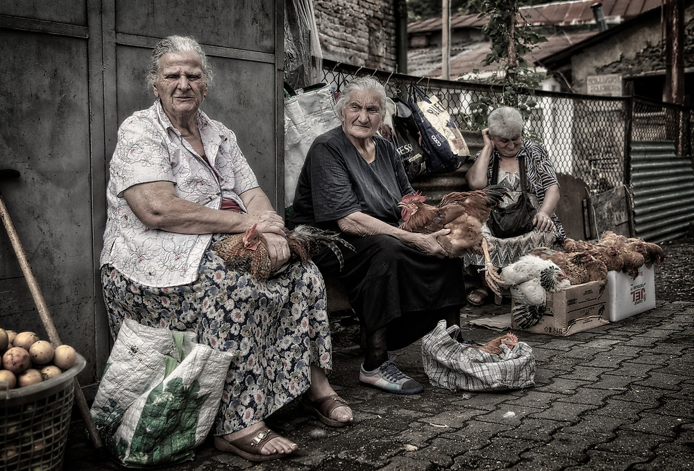 Three old women selling chickens at the market