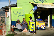 Bolivia.L a Paz. Two old women sit in the sun and eat ice creams.