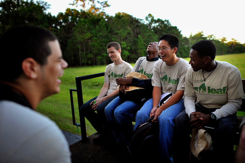 Grouped together on the back of a flatbed truck while traveling to sampling sites, interns with the Leaders in Environmental Action for the Future (LEAF) program share a laugh. The LEAF program works with environmental high schools across the nation to combine classroom lessons with real-world conservation work experience for urban youth.(Stephen Morton for The New York Times)