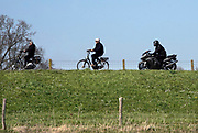 Nederland, Batenburg, 5-4-2020  Nu het wat warmer wordt en de zon uitbundig schijn halen motorbezitters hun tweewielers weer van stal en is het op de dijk langs de maas een drukte van belang van groepjes toerende motormuizen, fietsers en autos .Foto: Flip Franssen
