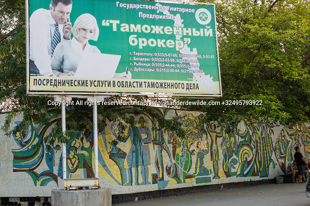 20150827  Moldova, Transnistria,Pridnestrovian Moldavian Republic (PMR) a modern billboard promoting administrative schooling at a bus station where a wall is still decorated with an old soviet mosaic in the same colors
