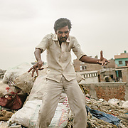 A cloth recycler dance at the end of his day. In Bhalswa district, north Delhi, a village is located right below one of the giant open air garbage dump which burns 24/7, creating toxic fumes.