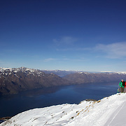 Skiers on top of Mount Albert on Minaret Station, Wanaka, with Lake Wanaka in the background. Wanaka, New Zealand. 31st July 2011