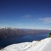 Skiers on top of Mount Albert on Minaret Station, Wanaka, with Lake Wanaka in the background. Wanaka, New Zealand. 31st July 2011