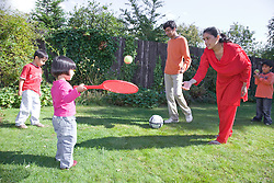 Young family playing with a racket and ball in the garden,