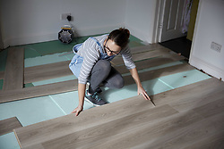 February 15, 2018 - Woman laying new floorboards in the living room of  a house under renovation. (Credit Image: © Mint Images via ZUMA Wire)