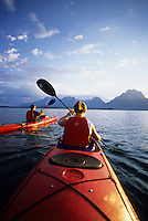 A young couple paddles sea kayaks on Jackson Lake in Grand Teton National Park, Jackson Hole, Wyoming.