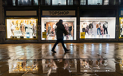 Edinburgh, Scotland, UK. 19 December 2020.  Views of streets and shops in Edinburgh City Centre on evening that Scottish Government announced the highest level 4 lockdown will be enforced from Boxing Day in Scotland.  Pic;  Member of public walks past Topshop in the rain at night. d. Iain Masterton/Alamy Live News