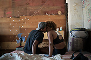 """In this Sept. 11, 2017 photo, Jayanne Pessanha, left, and Yara Andrade, kiss in their room in a squatter building that used to house the Brazilian Institute of Geography and Statistics (IBGE) in the Mangueira slum of Rio de Janeiro, Brazil. """"Those who are here have faith. They have faith that they will leave this place,"""" said Pessanha. (AP Photo/Felipe Dana)"""