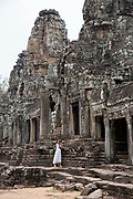A woman in a white bridal dress takes a photo whilst standing on the ancient stone structure of Angkor Thom, Siem Reap Province, Cambodia, South East Asia.