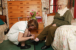Carer helping an elderly woman on with her shoes; homecare for the elderly,