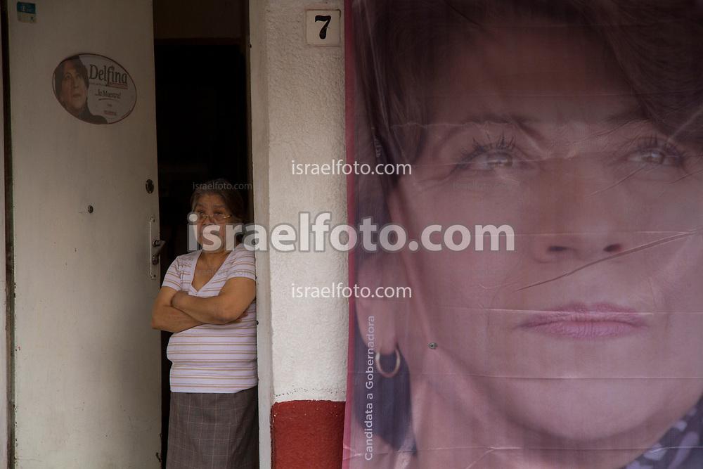 Una simpatizante de Delfina Gómez mira un mitin de la candidata desde la puerta de su departamento en Tlalnepantla.