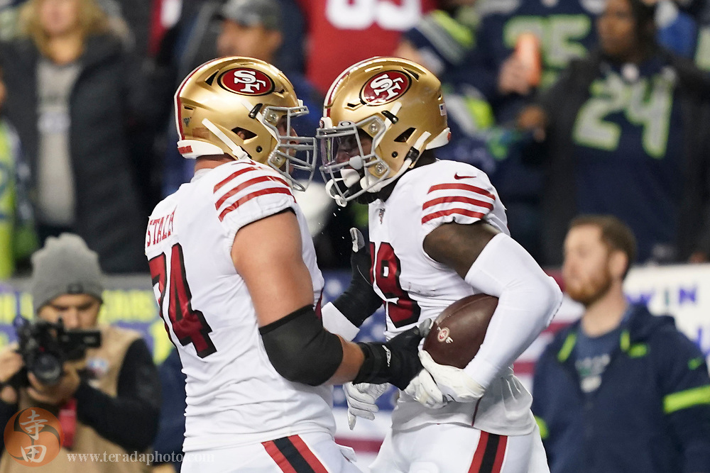December 29, 2019; Seattle, Washington, USA; San Francisco 49ers wide receiver Deebo Samuel (19) is congratulated by offensive tackle Joe Staley (74) for scoring a touchdown against the Seattle Seahawks during the first quarter at CenturyLink Field.