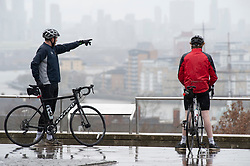 © Licensed to London News Pictures 26/03/2021. Greenwich, UK. Two cyclists brave the wet weather in Greenwich Park, London today during a third national coronavirus lockdown as heavy rain and strong winds make for a wet start to the weekend. Photo credit:Grant Falvey/LNP
