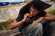 """A Honduran immigrant smokes a cigarette and cover himself from the raining with a piece of cardboard while waits beside of the railroad to climb """"the beast"""" or """"train of death"""", referring to the freight train where thousands of migrants travel with the intention of reaching to United States, in State of Mexico, Mexico, August 20, 2008."""