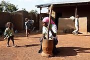 Abdulai Sadia prepares food while her children play around the home compound in the community of Kunayili, near Gushegu, Northern Ghana, on Wednesday November 2, 2011.