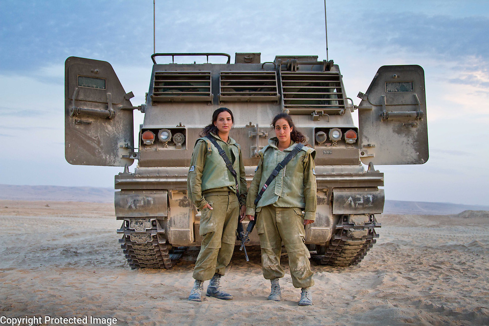 Two Israeli young women in army uniforms wearing large rifles stand in front of a large army vehicle in the Negev desert, Israel. Photo by Debbie Zimelman Photography, Modiin Israel
